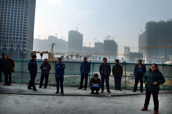 Local residents stand in front of a large construction site at the mega real estate project Huaguoyuan in Guiyang on February 12, 2015.
