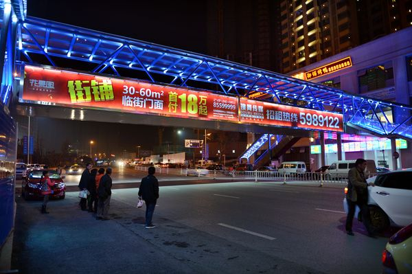 Sales and rental advertisement for retail shops plastered on the side of a footbridge outside the mega real estate project Huaguoyuan in Guiyang.